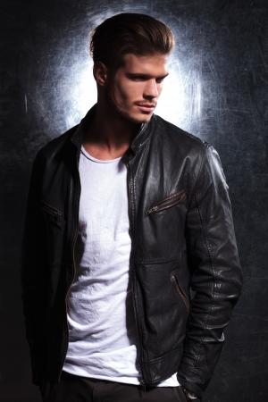chaqueta de cuero: sonriente hombre de moda usar una chaqueta de cuero que mira lejos de la c�mara, la imagen vista lateral