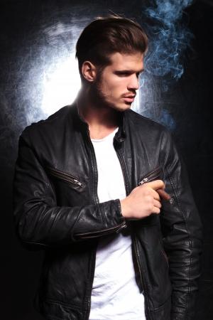 mann mit langen haaren: junge Mode-Modell in der Lederjacke rauchte eine dicke Zigarre und Wegschauen von der Kamera