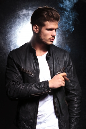 young fashion model in leather jacket smoking a big cigar and looking away from the camera