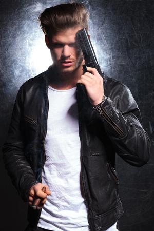 stílus: fiatal férfi bőrkabát szivarozott, és kezében egy pisztoly ellen fejét Stock fotó