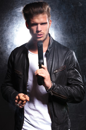 young killer man  in leather jacket blowing the smoke from his gun photo