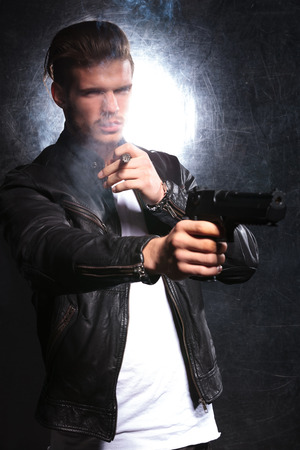 young fashion model dressed in leather jacket as a killer pointing his pistol away, while smoking a cigar