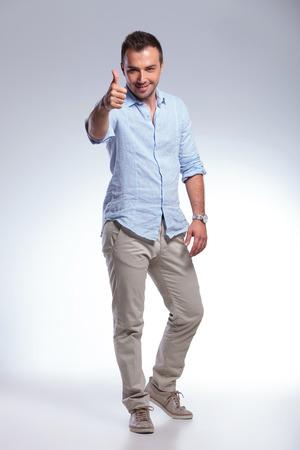 full length: full length Portret van een jonge casual man met de duim omhoog gebaar naar de camera. op een grijze achtergrond