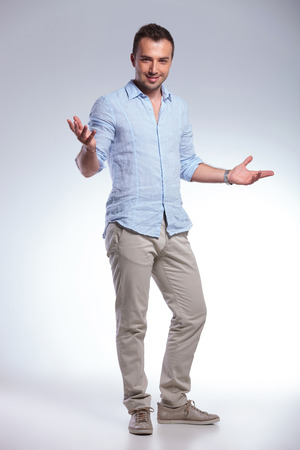 welcoming: full length of a young casual man welcoming you with his arms wide open and a smile. on gray background Stock Photo
