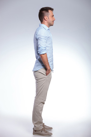 side profiles: full length side view of a young casual man with both hands in his pockets. on gray background Stock Photo