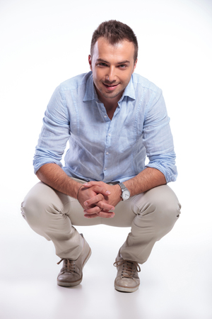 knees bent: young casual man posing in a crouched position with his hands together and smiling for the camera. on gray background