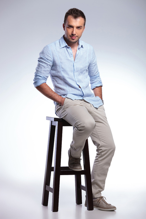full length picture of a young casual man sitting on a chair and holding both hands in his pockets. on gray background