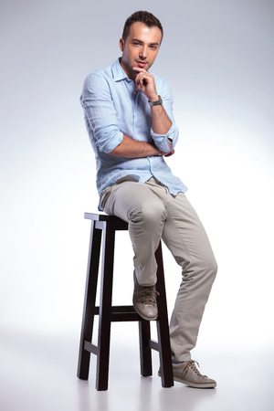 the stool: full length photo of a young casual man sitting on a chair and touching his chin while looking pensively at the camera. on gray background