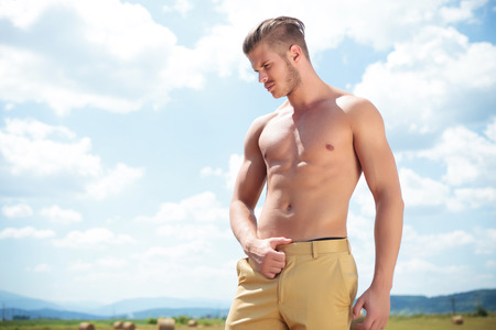 young topless man posing outdoor with hand on pants and looking down, away from the camera photo