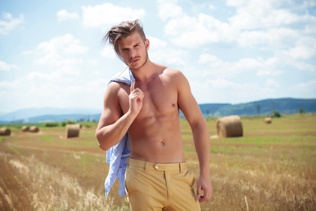 young topless man posing outdoor, on a cereal field, with a straw in his mouth while holding his shirt over his shoulder and looking into the camera photo