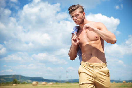 young topless man walking outdoor with a straw in his mouth and a shirt over his shoulder while looking away photo