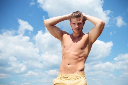 young topless man posing outdoor with both hands behind head while looking at the camera photo