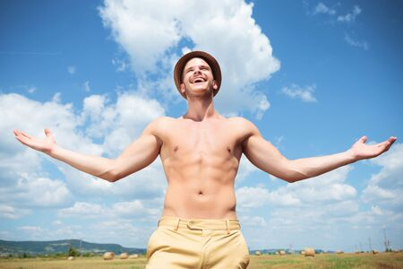 young topless man posing outdoor with arms wide open and a big thankful smile while looking at the sky photo