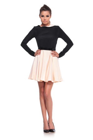 full length: full body foto van een jonge sexy vrouwelijk model in een korte jurk met handen op de heupen Stockfoto
