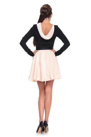 belles jambes: vue arrière image d'une jeune femme sexy dans une belle robe à la mode debout avec les mains sur les hanches