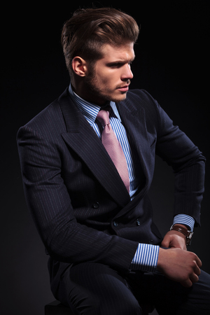 side view of a young fashion model in a classic suit and tie on dark background photo