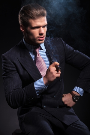 side view of a fashion business man smoking a cigar and looking away from the camera on dark background photo