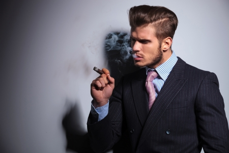 side view of a fashion model in suit and tie enjoying his cigar on gray background photo