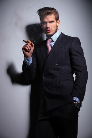 hombre fumando puro: hombre joven con traje y corbata con la mano en el bolsillo está fumando un cigarro sobre un fondo gris