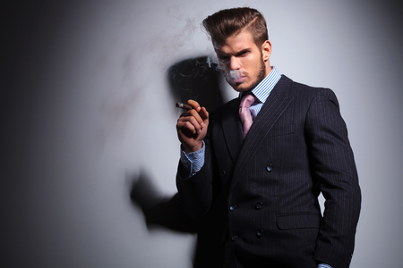 serious business man is smoking his cigar and looking at the camera on ggray background photo
