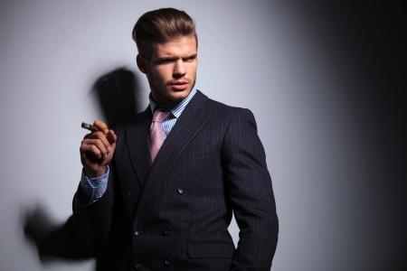 hombre fumando puro: hombre de negocios relajada en un juego clásico que fuma un cigarro y mirando a su lado en el fondo gris Foto de archivo