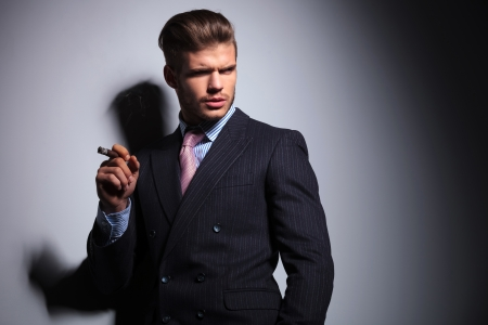 man smoking: relaxed business man in a classic suit smoking a cigar and looking to his side on gray background Stock Photo