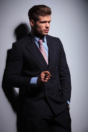 hombre fumando puro: vista lateral de un hombre de moda en traje y corbata fuma un cigarro en el fondo gris