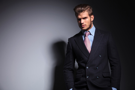 hair tie: relaxed young fashion man in suit and tie standing with his hands in pockets and looking at the camera on gray background Stock Photo