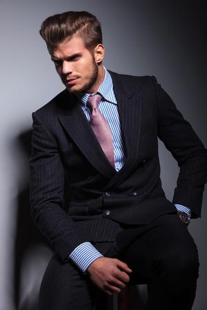 hombre sentado: cuadro del lado de un hombre enojado joven de negocios en traje clásico y corbata sentado en una silla y mirando a otro lado sobre fondo gris