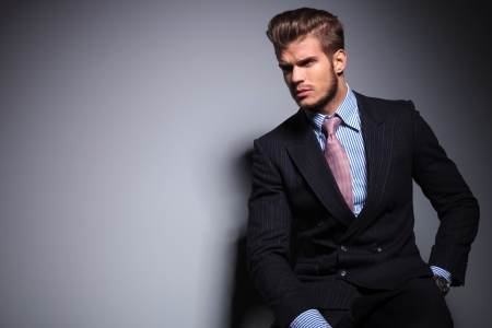 male hair: seated young fashion model in suit and tie is looking away to his side