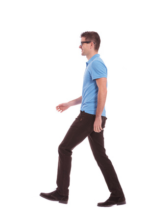 toward: side view of a young casual man walking and looking forward. on white background