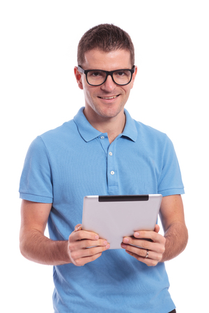 young casual man holding a tablet with both hands and smiling for the camera. on white background photo