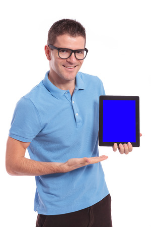 young casual man presenting a tablet with a blank blue screen while smiling for the camera. on white background photo