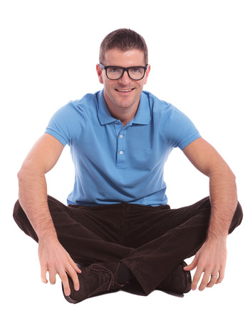 young casual man sitting on the floor with his legs crossed and smiling for the camera. on white background Stock Photo - 23005354