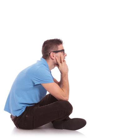 mani incrociate: vista laterale di un giovane casual uomo seduto con le gambe incrociate e guardando avanti, lontano dalla fotocamera. su sfondo bianco