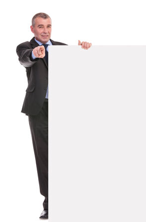 pannel: full length portrait of a business man presenting a blank pannel and pointing at the camera. on a white background