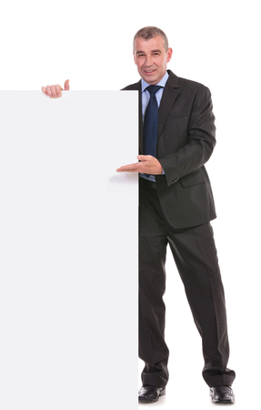 full length portrait of a business man presenting a blank board and looking into the camera. on a white background photo