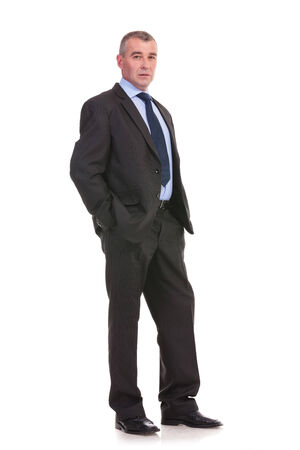 full length picture of a business man standing with his hands in his pockets and looking into the camera with a serious expression. on a white background photo