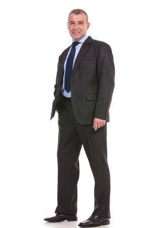 full length picture of a business man standing with a hand in his pocket and smiling for the camera. on a white background photo