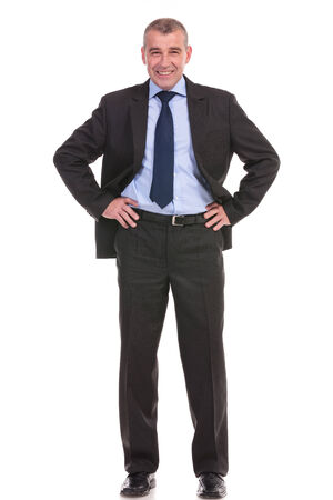 full length picture of a business man standing with his hands on his hips and smiling for the camera. on a white background photo