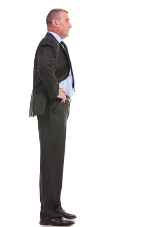 full length side view portrait of a business man standing with his hands on his hips and looking forward. on a white background photo