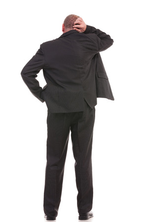 full length back view of a business man standing with a hand in his pocket and scratching his head with the other hand. on a white background photo