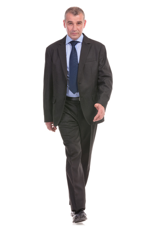 full length picture of a business man walking to the camera. on a white background photo