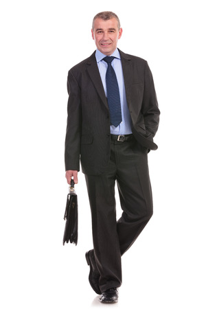 full length picture of a business man walking toward the camera with a briefcase in his hand and smiling while holding his free hand in his pocket. on a white background photo