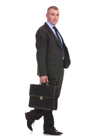 full length picture of a business man walking with a briefcase in his hand and looking into the camera. on a white background photo