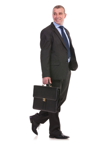business briefcase: full length picture of a business man walking with a briefcase in his hand and smiling away from the camera. on a white background