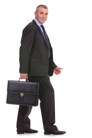 full length side view picture of a business man walking with a briefcase in his hand and looking at the camera with a smile on his face. on a white background photo