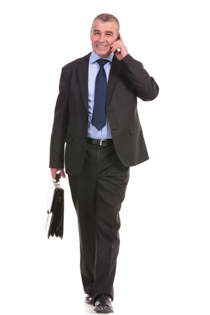 brief case: full length picture of a business man talking on the phone while walking toward the camera with a briefcase in his hand. on a white background Stock Photo