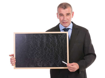 business man pointing with chalk at a blackboard he is holding while looking into the camera. on a white background photo