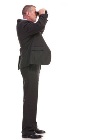 full length side view picture of a business man looking through binoculars. on a white background photo